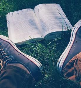 Un livre posé dans lherbe. Deux pieds apparaissent à proximité de l'ouvrage.