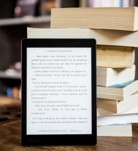Une liseuse posée à côté d'une pile de livres.