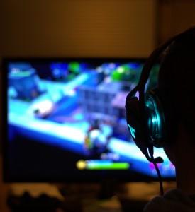 Une personne de dos jouant dans la pénombre à un jeu vidéo.