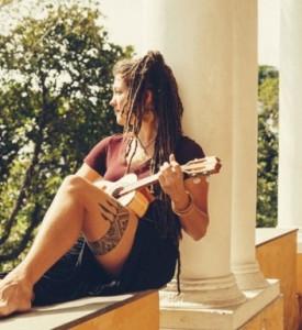 Photo de l'artiste, assise sur un muret, en train de jouer du ukulele