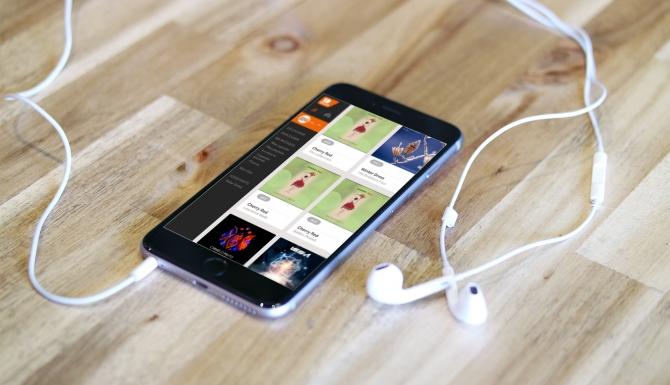 smartphone posé sur une table avec ses écouteurs. Sur l'écran on voit la page d'accueil d'1D Touch