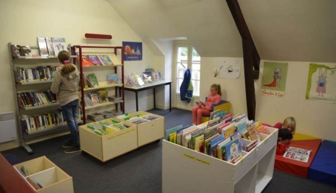espace enfants, moquette grise, tapis de couleur bleu et rouge, rayonnages et bacs