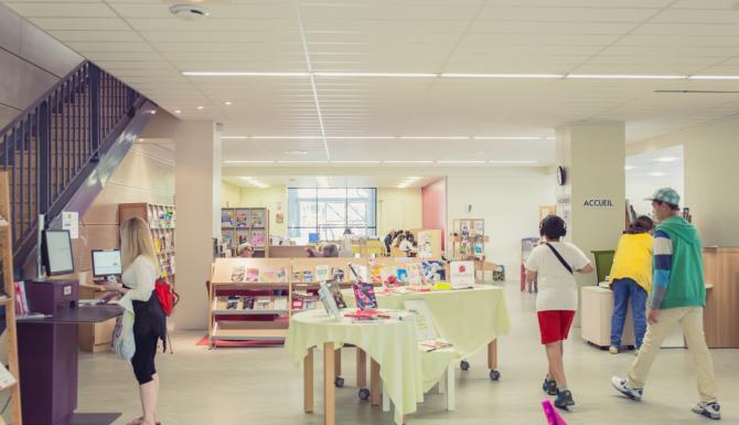 Espace central avec automates de prêt, tables de présentations et vue sur les collections