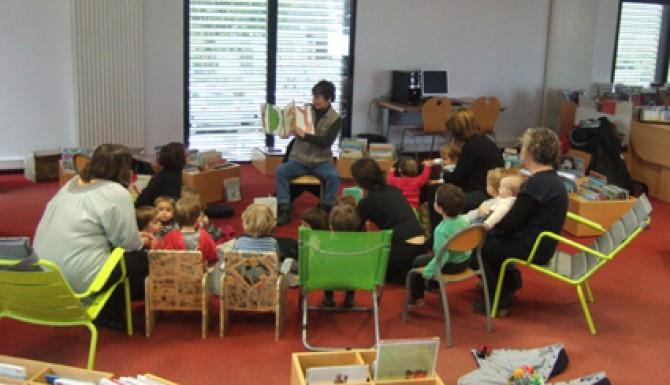 Accueil de petite enfance à la bibliothèque d'Acigné. Le bibliothécaire montre le livre qu'il conte à un groupe d'enfants en rond sur des tapis