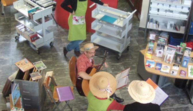 Animation jardins à Acigné. Des personnes habillées avec des tabliers de jardinage et des chapeaux de paille chantent et s'accompagnent à la guitare
