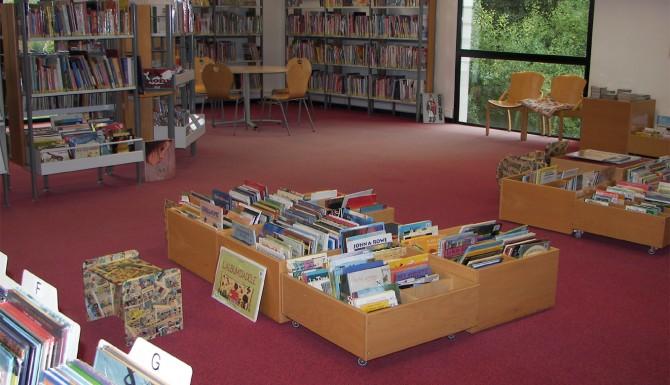 Acigné, photographie de l'espace jeunesse. Moquette rouge et des bacs posés au sol contenant des albums