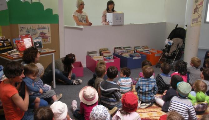 Animation autour de contes : public jeune rassemblé autour de deux bibliothécaires