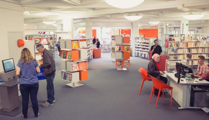Autre vue des espaces. on y vois un autre automate de prêt, l'accueil, des chaises rouges, des meubles à revues oranges et au fonds le reste des collections