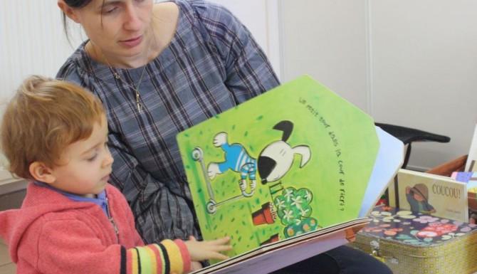 bibliothécaire lisant un album à un enfant
