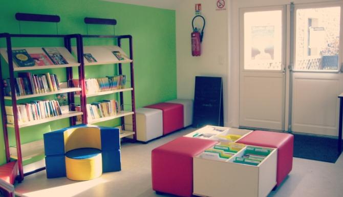 Entrée de la bibliothèque, avec les bacs et assises jeunesses. Le mur de gauche est vert