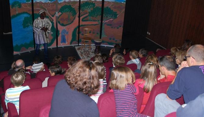 Animation autour de contes africains : public rassemblé dans un auditoium. Sur la scène un conteur.