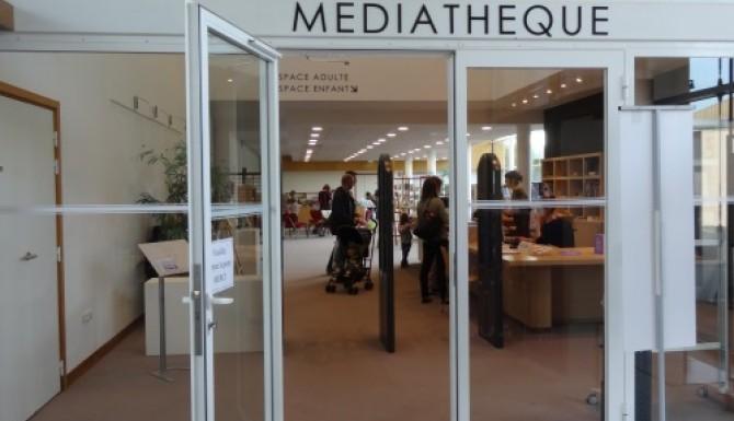 entrée de la médiathèque. porte vitrée séparant le hall du centre culturel de la médiathèque à droite de l'entrée.
