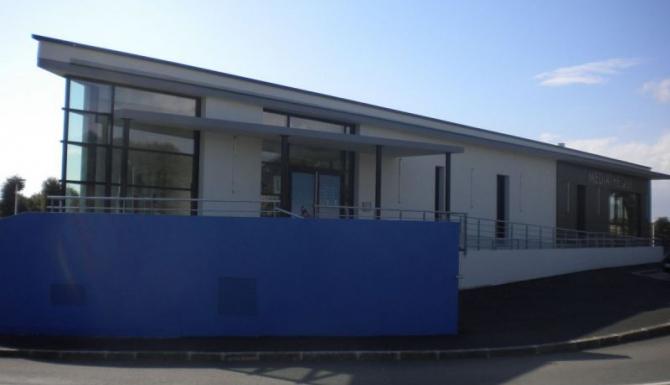 extérieur du bâtiment. Majorité blanc et gris et un mur très bleu