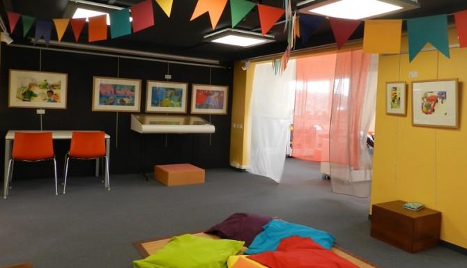 coin enfant très coloré avec des coussins colorés au sol, des chaises et des fanions accrochés au plafond
