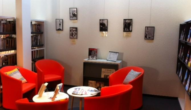 Salon de lecture avec des fauteuils cosy rouges et tables basses. Au fonds, on voit une exposition