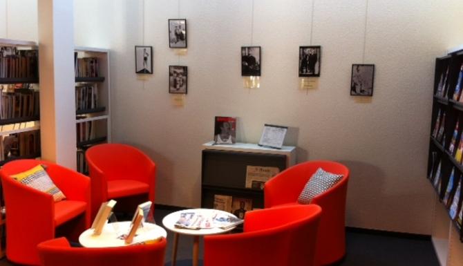 Bibliothèque Landry - Salon de lecture avec des fauteuils cosy rouges et tables basses. Au fonds, on voit une exposition
