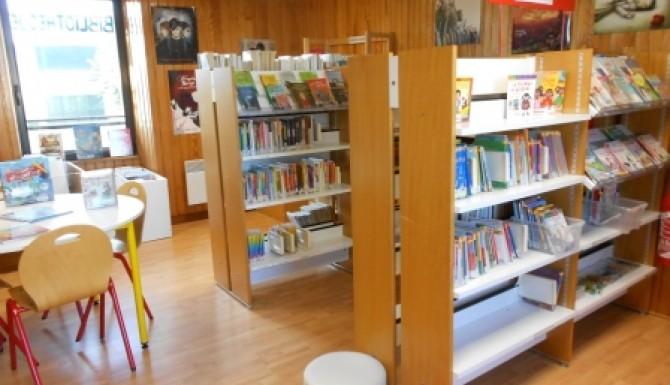 espaces de la bibliothèque. Environnement majoritairement en bois. Rayonnages, tables enfants et pouf blanc