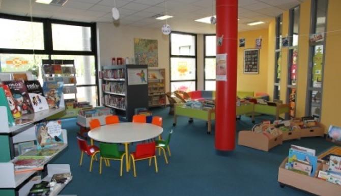 autre vue de l'espace jeunesse où on aperçois des tables et un pilier rouge vif