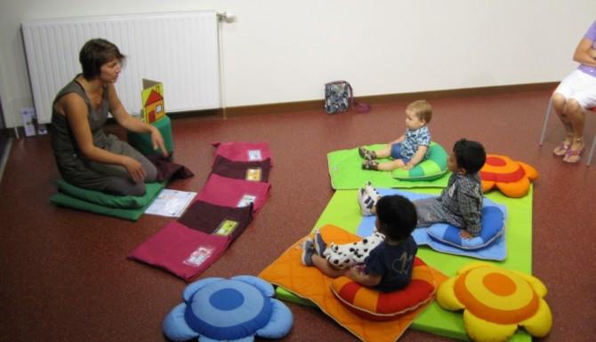 animation enfant avec une bibliothécaire et des enfant ssur des tapis en formes de fleurs de couleurs vives