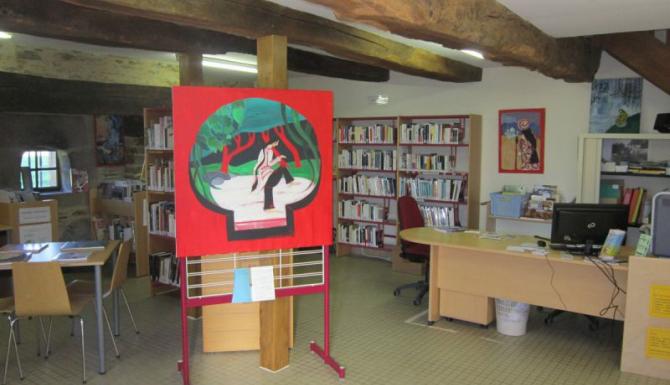 vue des espaces, du bureau d'accueil, des rayonnages et d'un panneau d'affichage rouge, sur lequel est accroché une peinture d'inspirations asiatiques