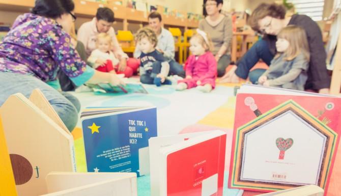 espace des enfants. Des livres jeunesse en premier plan et des adultes et leurs enfants en second plan