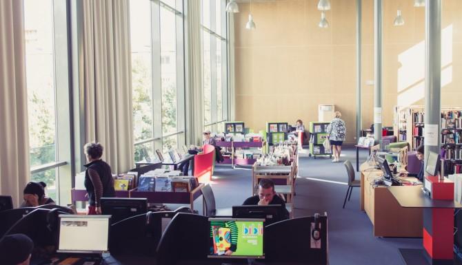 au premier plan l'espace multimedia, des ordinateurs en vis à vis. En arrière-plan, l'automate de prêt de couleur rouge, et des bacs d'albums et BD de couleur violette et verte.