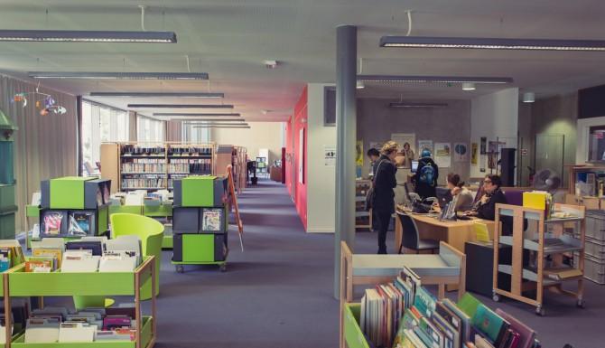 espaces de la bibliothèque. On y aperçois l'accueil, des bacs de couleur verte contenant des BD et des albums. Murs rouges et moquette mauve