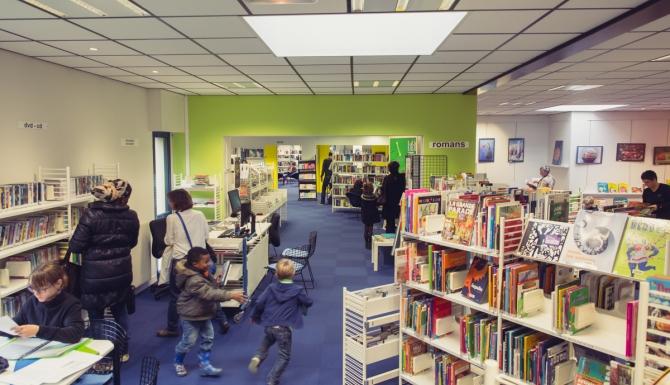 Cleunay - Espaces de la médiathèque et usagers. Rayonnages blancs, moquette en quadrillages de bleus, murs du fonds verts