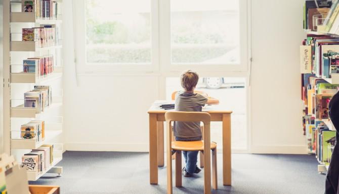 coin jeunesse. Un enfant lit assis sur une petite chaise/table. Des mangas sont aperçus à gauche et des albums à droite