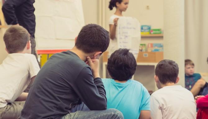 animation jeunesse. Au premier plan des enfants, au second plan un animateur et une jeune présentant leur travail