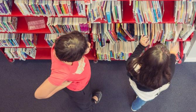 espaces vu du dessus, des personnes cherchent des livres dans une étagère rouge