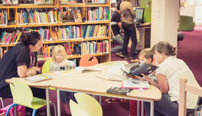enfants et parents lisant des albums assis sur des chaises