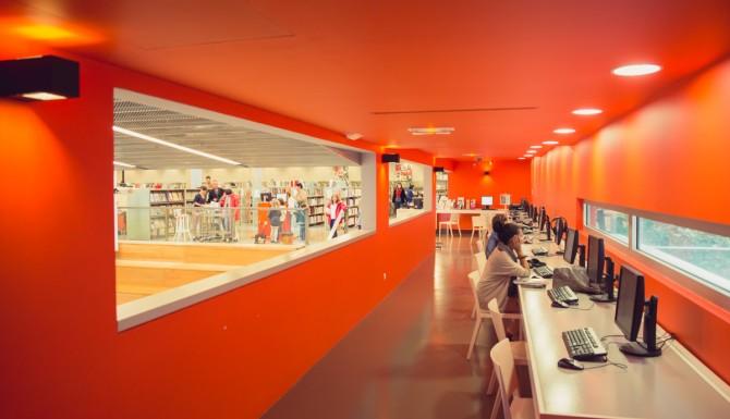 espace multimédia le long d'un couloir orange, percé d'une grande baie vitrée