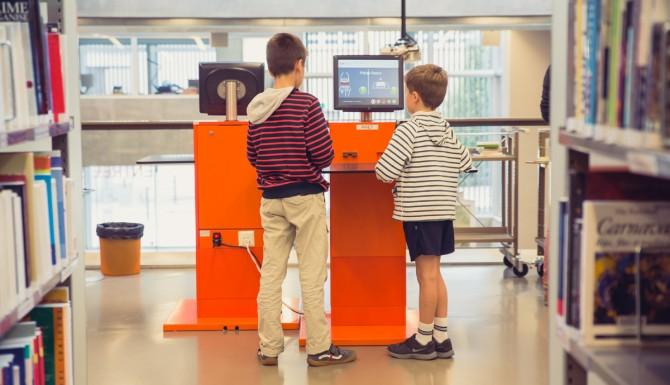 enfants utilisant les automates de prêt oranges