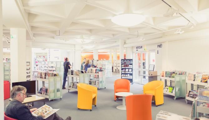 espaces où l'on peut voir, des usagers, des bacs, des fauteuils de couleurs, un automate de prêt et un catalogue consultable