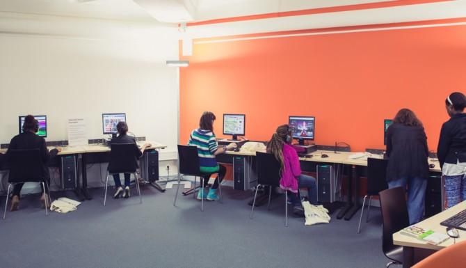 Espace multimédia, des tables munies d'ordinateurs disposées le long des murs rouges et blancs