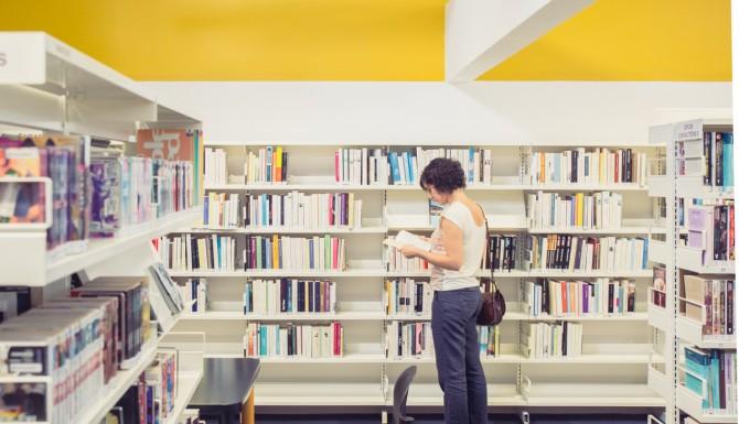 espace romans, des rayonnages blancs, un mur jaune et une personne feuilletant un livre