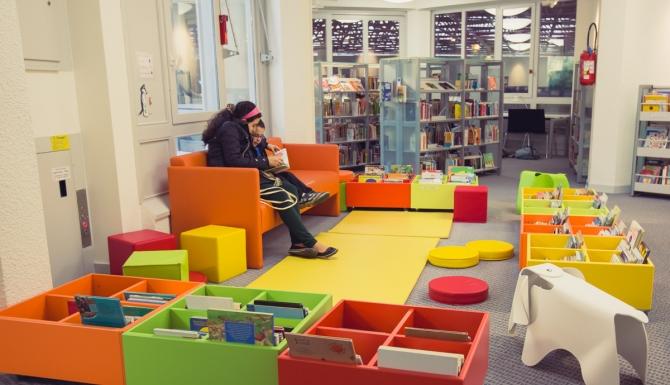 Bibliothèque Triangle - Espace enfants, très coloré. Banquette orange, tapis et bacs de toutes les couleurs. Un siège en forme d'éléphant