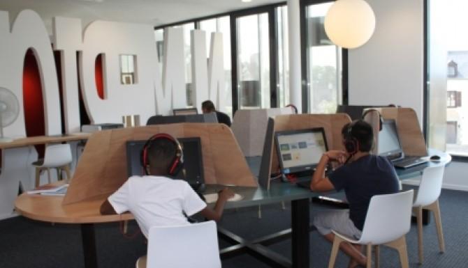 Espace multimédia. enfants autour d'ordinateur
