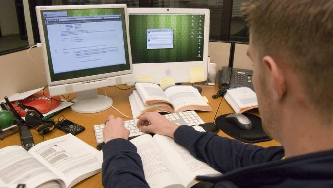 Personne photographiée de dos travaillant devant un écran d'ordinateur