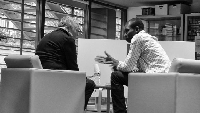 photo en noir et blanc de deux hommes discutant assis dans des fauteuils