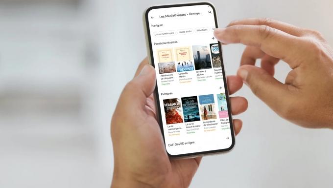 Zoom sur des mains tenant un smartphone. l'écran affiche la nouvelle application Aldiko