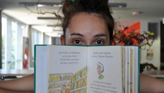 Jeune femme avec la partie basse du visage dissimulée derrière un livre. Paire de lunettes au premier plan.