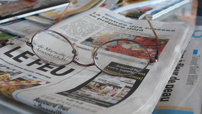 Paire de lunettes posée sur des journaux