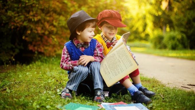 Deux enfants lisant ensemble des livres sur le bord d'une route ensoleillée à la campagne.