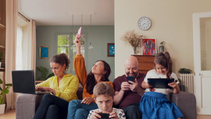 Une famille rassemblée dans son salon. Chacun des membres utilisent un appareil numérique.