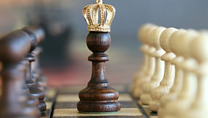 Jeu d'échecs. Un pion est placé au centre coiffé d'une couronne dorée.