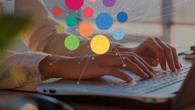 Le logo (points de couleurs) est affiché au dessus de l'image de mains d'une personne tapant sur un clavier d'ordinateur portable