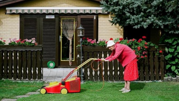 grand mère habillée en fushia poussant une tondeuse dans un pavillon