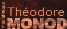 Logo rectangulaire de la médiathèque Théodore Monod de Betton. Texte orangé sur fond marron fonçé.